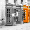 Five London Telephone boxes all in a row in black and white - one Orange
