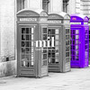 Five London Telephone boxes all in a row in black and white - one Purple