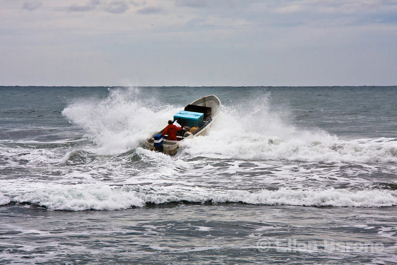 Fishing boat in surf, Madresal eco beach camp and reserve, Pacific Coast, Chiapas, Mexico.