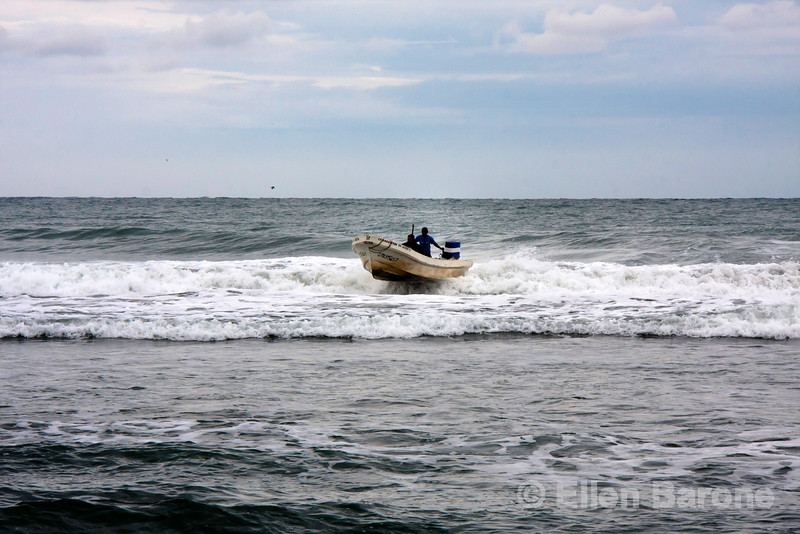 Fishing boat rides the surf in at Madresal eco beach camp and reserve, Pacific Coast, Chiapas, Mexico.