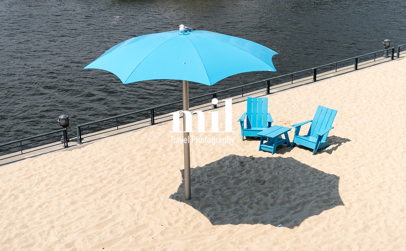 Two blue chairs with parasol on a city beach