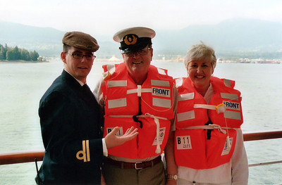 Mom & Dad at lifeboat drill with the captain, who tries a hat swap with Dad