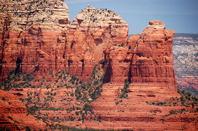 The vivid hues of red rocks, green trees, and blue sky create striking contrasts