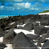 Another white sand beach with black lava rocks throughout.