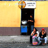 Otavalo Market<br /> <br /> This is one of the picture in my series Otavalo Doorways. This picture was taken two blocks from the main Otavalo marketplace. These three women were chatting about other people while sitting on the sidewalk beside the doorway to a kitchen. Their male friend supply them with foods and drinks. I think this photo shows how relaxed the way of life is in this northern town of Ecuador.