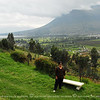 My wife Beth standing on a low hill with the Cayambe mountain beyond and the town of Cayambe seen below. Cayambe mountain is a volcano.