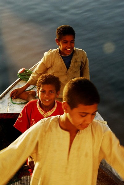 The three are all very young like the boy and girl on the other boat.
