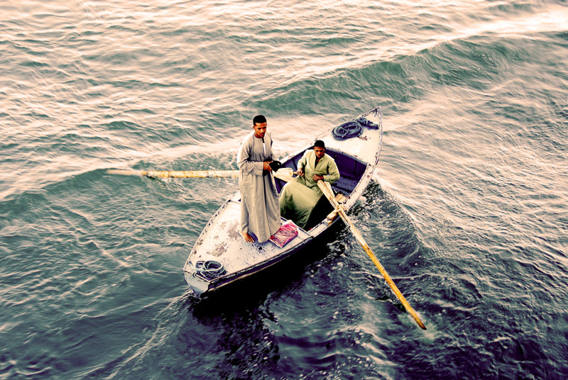 Another boat of water vendors approaching the ship. A plastic wrapped clothing is lying by his feet.