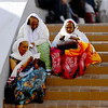 Three Gypsy Women resting on the steps of a stairway in the mall adjacent to Four Seasons Hotel.
