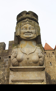 "From Rick Steves' Guidebook:  ""1,200 years ago Charlemagne besieged this town, then called La Cité, for several years.  Just as the town was running out of food, Madame Carcas (portrayed in this statue) fed the last bits of grain to the last pig, and then threw him out over the city wall.   Surprised that the town could afford to throw fat party pigs over the wall, Charlemagne's tired army decided they would never succeed  in starving the people out.  They ended the siege and the city was saved.  Madame Carcas sounded the victory bells.  The French word for the verb ""to sound"" is ""sonner"", and hence the city got a new name ... Carcas-sonne."""