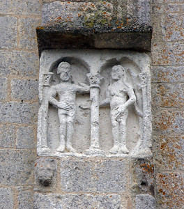 Adam and Eve depicted on the side of the Romanesque church.