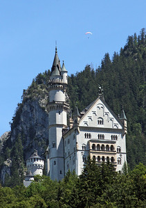 Neuschwantein, Mad King Ludwig's most famous castle, sits up on the mountainside above his boyhood hometown of Hohenschwangua.  This is a telephoto shot of it as seen from our hotel room.  Note the hang glider above the castle.