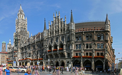 "The ""New"" City Hall on Marienplatz (built 1867-1908); the ""Old"" Town Hall is nearby, but was rebuilt after total destruction by WWII bombs.  This is 6 vertical images stitched together side-by-side in order to get it all into one frame.  Note the lady in blue at lower left who appears in more than one of the frames as she walked by during my shooting; other ghosts appear for the same reason."