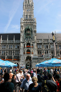 Crowds gather on Marienplatz to hear and watch the new City Hall glockenspiel, which operates 3 times per day.  The glockenspiel  characters move in the two tiered spaces in the tower that are above the flowered balconies you see here.