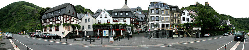 A multi-image panorama of the town of Beilstein as seen from down by the edge of the Mosel River.  The road in the foreground is actually straight; the apparent bend is induced by the panoramic processing.