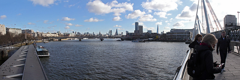 A multi-image panorama view down the Thames River from the Golden Jubilee Bridge, which appears on the right.
