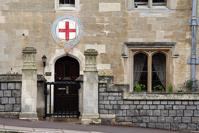 The emblem above this door in the Garter House is the symbol of The Most Noble Order of the Garter, founded in 1348,.  It is the highest order of chivalry and the third most prestigious honour (inferior only to the Victoria Cross and George Cross) in England and the United Kingdom. It is dedicated to the image and arms of Saint George, England's patron saint.