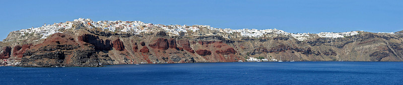 "A 7-image panorama of our first view of Santorini from our ferry.   The hilltop town you see here is Oia (""ee-ya"") where we will stay for 3 nights, and of which you will see many photos!   Our B&B is near the right end."