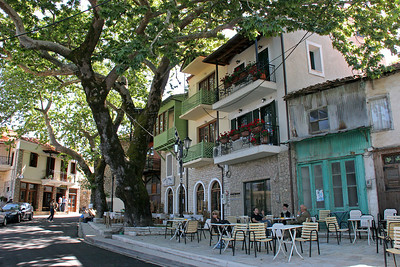 Andritsaina's central village plaza.  I loved how the enormous Sycamore tree gave it shade.  Notice Teddie at a table, and also the orthodox priest and friends near the blue doors.