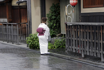 Tending the front of a wooden tea house, or Ochaya, in the Gion Geisha district.