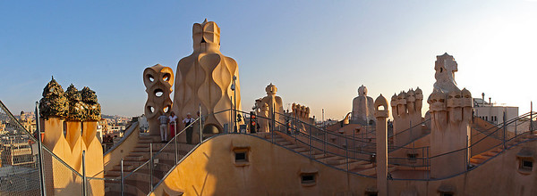 A 4-image pano on the roof of Casa Milà.  The long foreground curve is the top edge of the central courtyard opening.