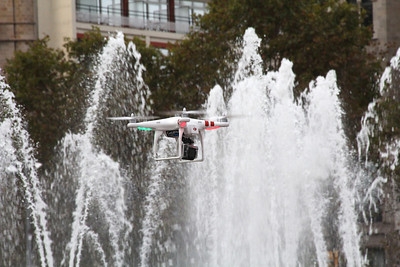 A model helicopter hovers above a fountain in Plaça de Catalunya.