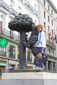 A tourist embraces the statue of a bear in Puerta del Sol.  The bear has been the symbol of Madrid since medieval times.  He eats berries from a Madroño tree which are used to make a local liqueur.