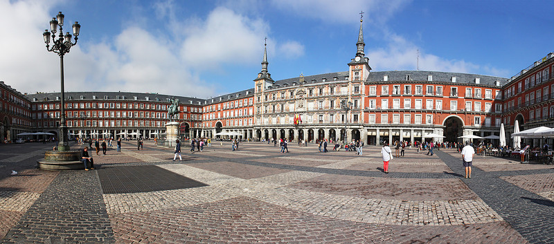 """A panorama of 9 vertical images side by side to capture much of Plaza Mayor.  The white umbrellas in the far corner are in front of """"La Torre del Ora Bar Andalú"""", a """"temple"""" of bull fighting, as will be shown in the next series of photos."""