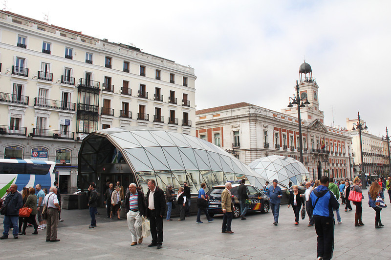 """The """"glass-fish""""  entrances to the subway on Puerta del Sol.  The county governor's office is the red and white building to the right."""