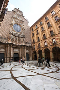 Basilica courtyard.  (5 images stacked vertically).  Our journey to visit La Moreneta moves to the left down the passageway under the arches at right.