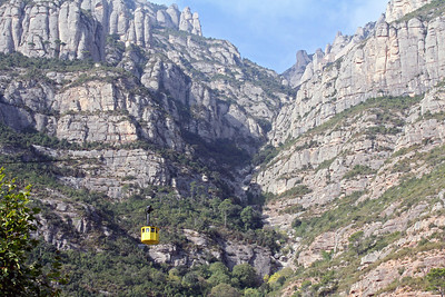 "First view of the monastery, barely visible, high up on the ridge above the train station.  The monastery's name, Montserrat, means ""serrated mountain"", for reasons that should be evident in this image."