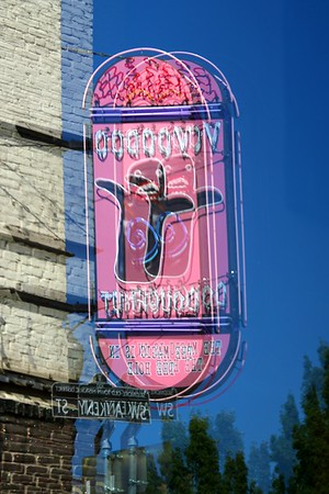 A reflection of the Voodoo Doughnut sign in a store window.  Loved the pink against the blue sky