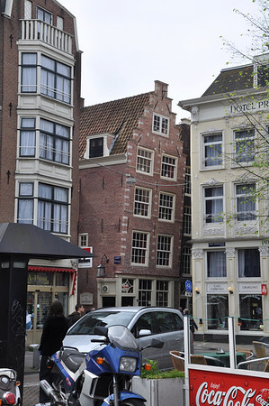 No, it's not the leaning apartment of Amsterdam.  It's built this way so that items of furniture, etc. can be raised via a rooftop pulley system without smashing into the lower windows.  Throughout the city, staircases are narrow and steep necessitating this type of outside lift.