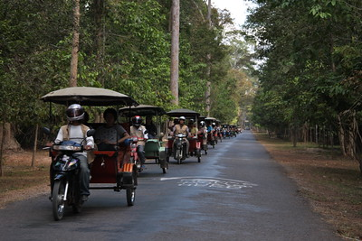 a row of tuk tuks touring people around Ankor Wat
