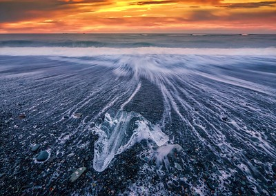 Long exposure shot of piece of ice swept onto a black beach by a wave during a dramatic sunset. This is the last remnant of a melting iceberg from Jokulsarlon Lagoon in Iceland.