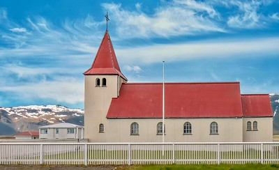 A typical rural church in West Iceland, with clean, simple lines and a red roof, and snow-covered hills in the background.