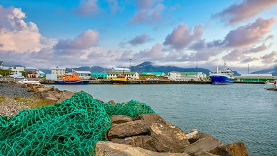 A green fishing net in the foreground of a picturesque landscape shot of a small, colorful fishing village on the coast of West Iceland, with fluffy sunset clouds in the background.