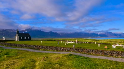 A wide angle view of the quaint Black Church of Budir and its small cemetery, set against mountains and the sea, on the Snaefellsnes Peninsula in West Iceland.