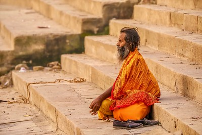 An Indian sadhu sits cross-legged in meditation on the public ghats of the ancient city of Varanasi at dawn.