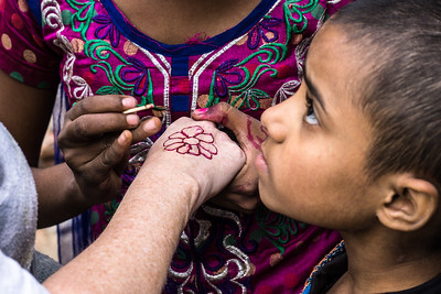 Kris, a Habitat for Humanity team member, gets a henna treatment from the neighborhood girls.