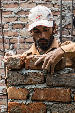 The lead mason building Hasina Bibi's house makes sure the top brick course is level.