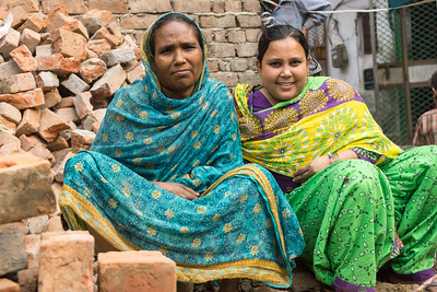 Hasina with a friend, sitting on the pile of bricks that would eventually become part of the structure of her home.