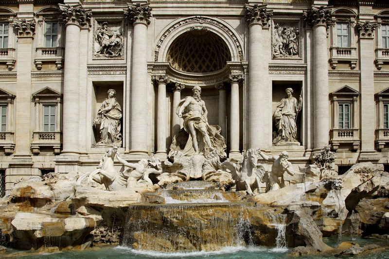 In 1629 Pope Urban VIII, finding the earlier fountain insufficiently dramatic, asked Bernini to sketch possible renovations, but when the Pope died the project was abandoned. Bernini's lasting contribution was to resite the fountain from the other side of the square to face the Quirinal Palace (so the Pope could look down and enjoy it). Though Bernini's project was torn down for Salvi's fountain, there are many Bernini touches in the fountain as it was built. An early, striking and influential model by Pietro da Cortona, preserved in the Albertina, Vienna, also exists, as do various early eighteenth century sketches, most unsigned, as well as a project attributed to Nicola Michetti one attributed to Ferdinando Fuga and a French design by Edme Bouchardon.<br /> <br /> In the center is superimposed a robustly modelled triumphal arch. The center niche or exedra framing Oceanus has free-standing columns for maximal light-and-shade. In the niches flanking Oceanus, Abundance spills water from her urn and Salubrity holds a cup from which a snake drinks. Above, bas reliefs illustrate the Roman origin of the aqueducts.<br /> <br /> The tritons and horses provide symmetrical balance, with the maximum contrast in their mood and poses (by 1730, the rococo is already in full bloom in France and Germany).
