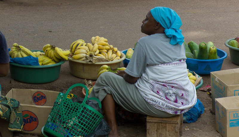 The people make a living however they can. This street vendor is selling fruit.<br /> <br /> She is wearing a kanga, a traditional garment made from 2 large pieces of wrapped fabric. A kanga typically has a phrase or folk saying printed on its fabric.
