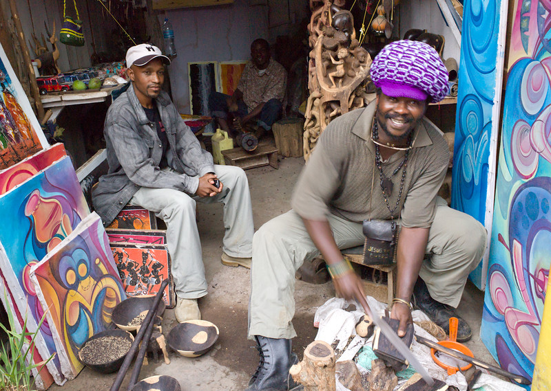 "Carvers in Arusha's Mount Meru (Masai) Market working with ebony. Ebony has a dark core surrounded by lighter wood, and ""real"" ebony carvings often have light and dark patches.  <br /> <br /> I bought a carving of a hippo from this friendly fellow."