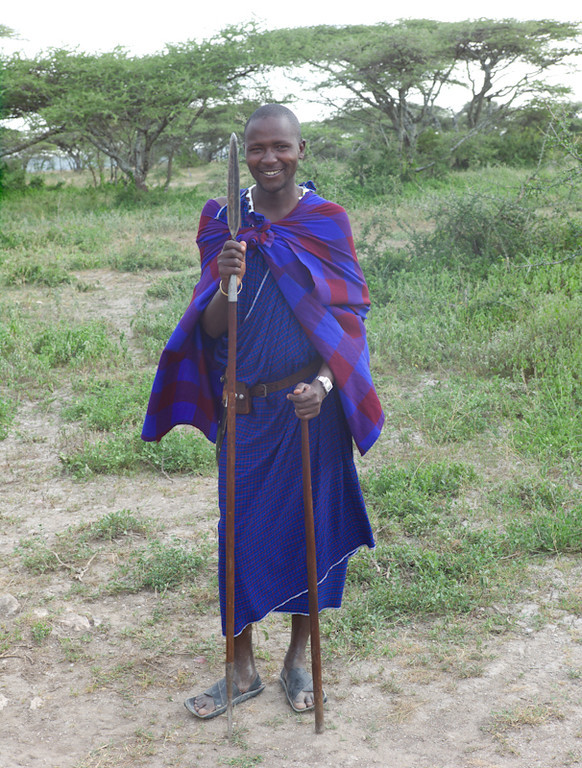 © Robert Will 2013<br /> <br /> Nata is a Masai guide who leads us on hikes from Ubuntu - the first to the nearby Hippo Pool, and the second to a viewpoint overlooking Lake Eyasi. <br /> <br /> Safari Camps in Tanzania are not fenced, so they hire local Masai as security against predators, and as guides. <br /> <br /> Men always carry a stick and a knife. When they are in the wild, they also carry spears. In the past, a young Masai would be required to kill a lion with his spear as a right of passage to manhood.  <br /> <br /> I asked Nata how old he is.  About 20, he thinks.
