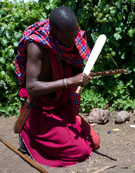 A demonstration of fire making. This fellow is shaving a stick to expose fresh wood, and to create wood shavings.