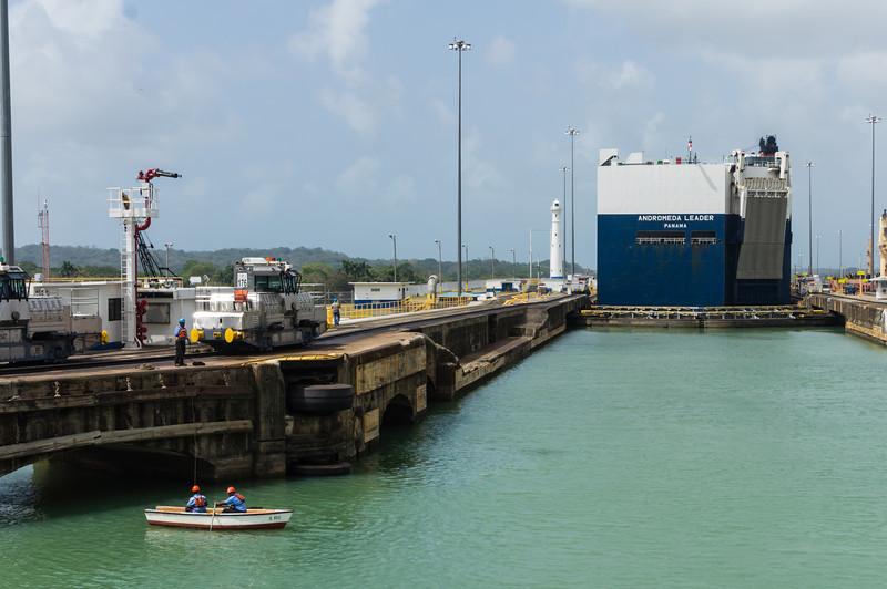 """A Study in Contrasts<br /> This is the first of the Gatun Locks (looking north).  To the left is a small row boat, which is used by the Panama Canal workers to catch ropes tossed to the boats making the transit.  To the right you see the back of a car carrying ship, the maximim sized ship allowed through the canal (a """"panamax"""" vessel), making its way from the Pacific Ocean to the Atlantic Ocean."""