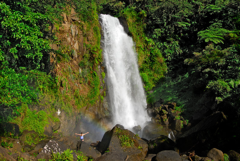 <b>Daphne outstretched at Trafalagar Falls</b><br/>   (Mar 19, 2006, 04:25pm)  <p align=left>This is a picture of the lower Trafalgar Falls (the one on the right).  That's Daphne standing with her arms outstretched, giving the waterfall scale.  And there is a nice rainbow arching over Daphne's head.</p>  <p align=left>(Gallery: Travel Journals > Dominica 06 > Dominica - March 19-20)</p>