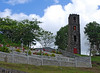 <b>Church grounds in Southeast Dominica</b>   (Mar 24, 2006, 10:42am)  <p align=left>We visited the outside of a church in  Southwestern Dominica.  This is a picture of the graveyard and tower behind the Catholic Church of St Gerard in Bellevue Chopin (thanks to David Michael for the identification).</p>